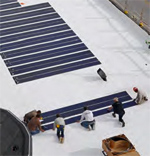 Construction workers laying solar panels on roof of building