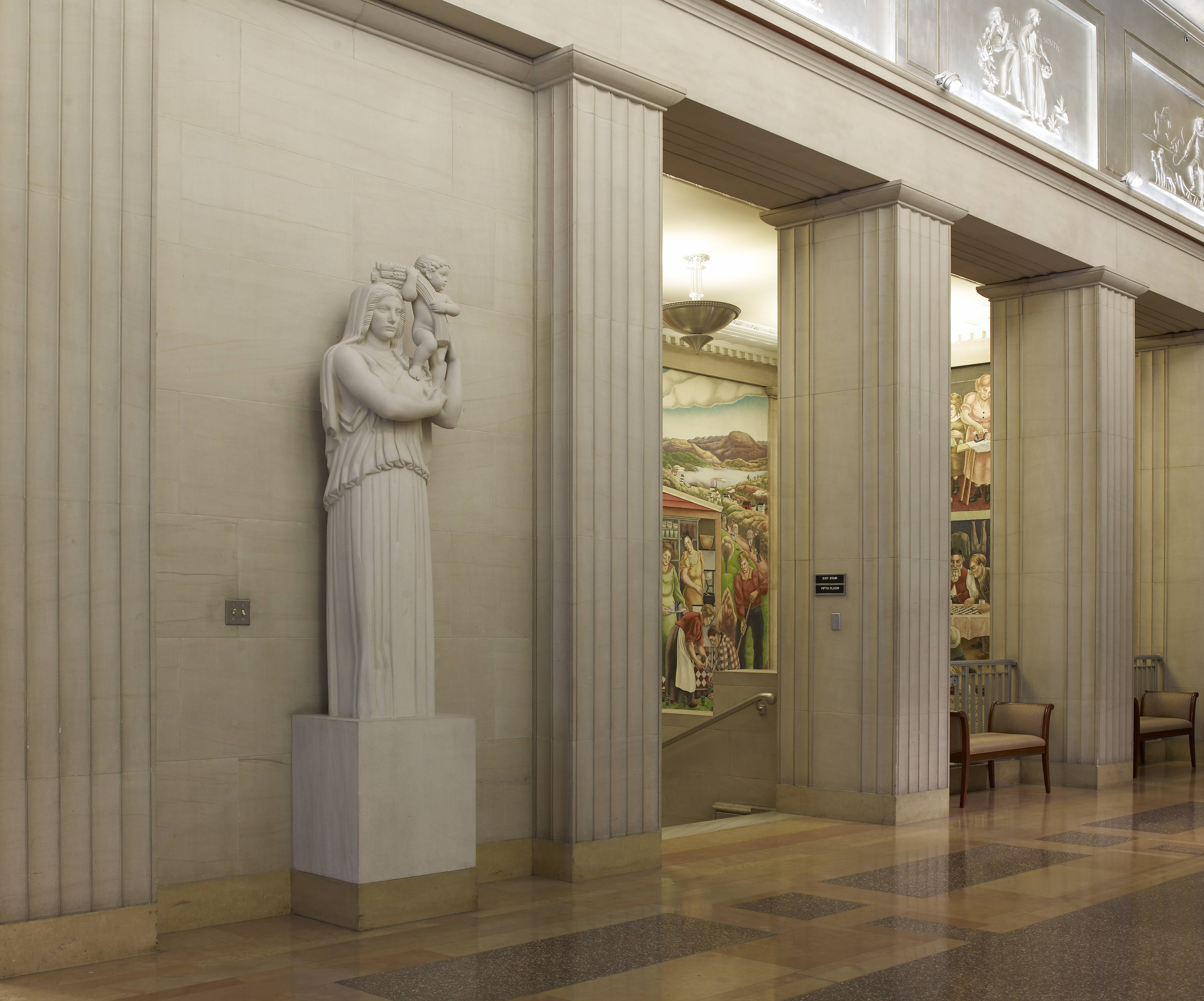 View of the 5th floor lobby, including Jennewein's Earth, in the foreground and George Biddle's fresco series, Society Freed Through Justice in the background.