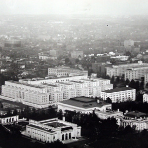 Aerial photograph, taken shortly after the completion of the Stewart Lee Udall building (lower left), the new Interior building dwarfed its neighboring buildings. The old three-wing Interior building can be seen across E street.