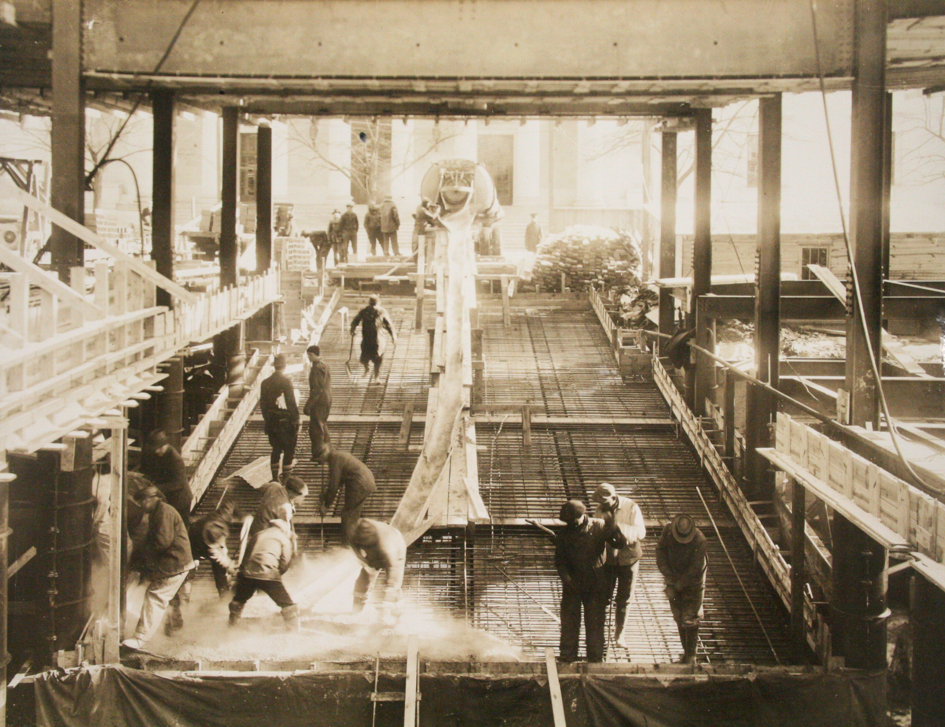 Workers pouring concrete during construction, C. 1935.