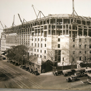 Construction of the Justice building's limestone facade. Trolley cars are visible along Constitution Avenue in the foreground.