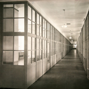 Historic photograph of interior corridor and office space. Glass partitions allowed natural light to penetrate the building's interior.