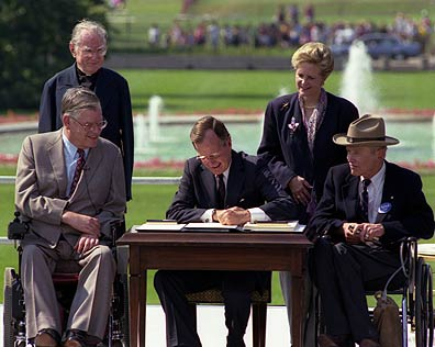 President George H.W. Bush signing Americans with Disabilities Act of 1990 on the South Lawn of the White House. L to R, sitting: Evan Kemp, Chairman, Equal Employment Opportunity Commission, Justin Dart, Chairman, President's Committee on Employment of People with Disabilities. L to R, standing: Rev. Harold Wilke and Swift Parrino, Chairperson, National Council on Disability, 07/26/1990
