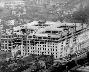 Construction of the IRS building's limestone facade. The four symmetrical interior courtyards are visible from the roofline.