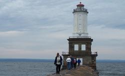 Medium shot of Keweenaw Waterway lighthouse and people walking on the pier