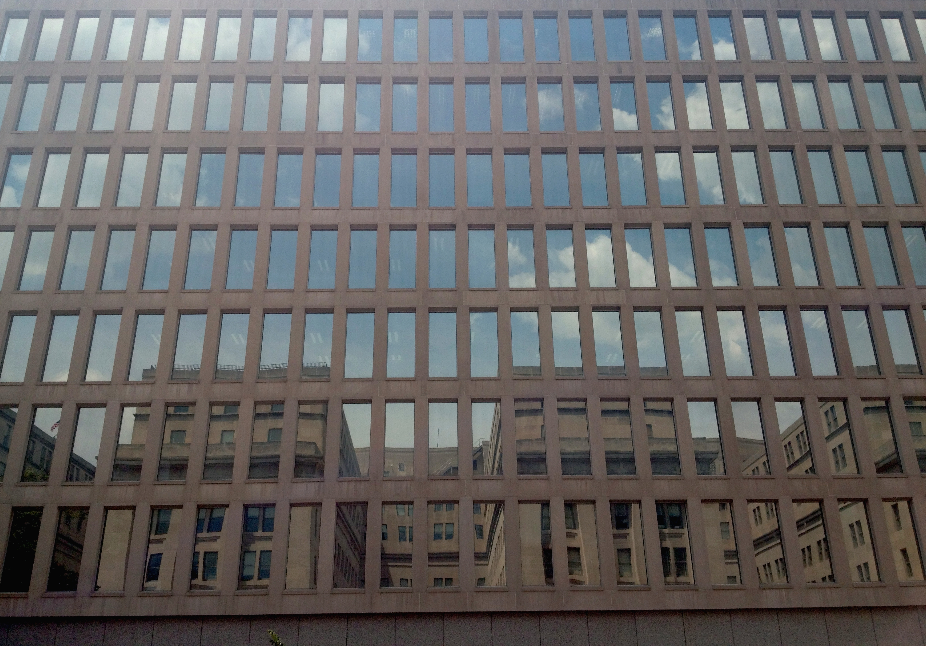 Reflection of the Stewart Lee Udall Department of Interior building in the windows of the Roosevelt building.