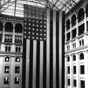 A large American flag hangs from the atrium in the Old Post Office.