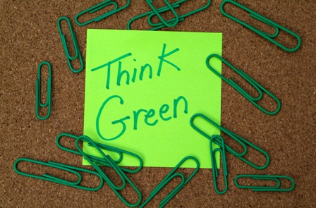 Bulletin board with green paper clips and sticky note that reads think green