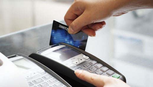 Photo of a credit card being swiped in a card scanner
