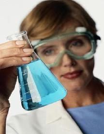 Female scientist examines a beaker of blue liquid.