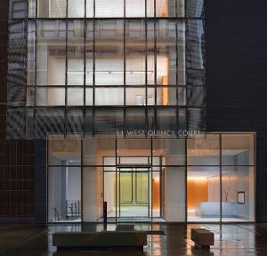 Exterior night shot of the new glass-walled entrance to the Quincy Court building