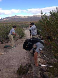 Three Americorps members working on a trail in New Mexico