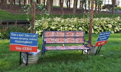 An artwork bench made of license plates and signs announcing it's title with trees in background