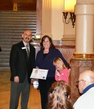 Lt. Colorado Governor Garcia presents Diane Authier, GSA employee, with a certificate and honorable mention