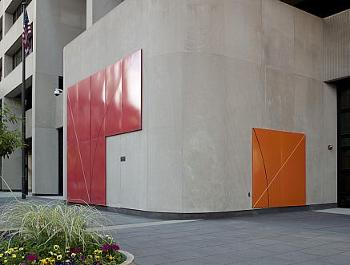 Plaza-level view of art wall with red T shape on front and orange square around corner right both with diagonal and arc lines