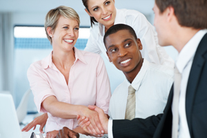 Stock photo of group of business people shaking hands over a computer