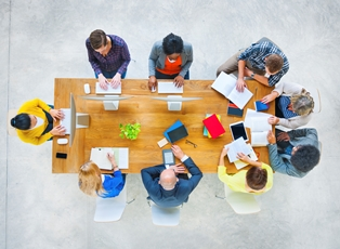 Group of 10 people sitting around a table working together