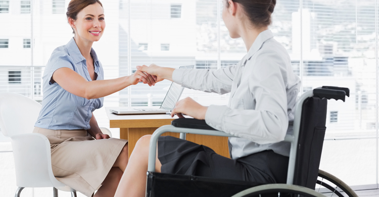 Image of a woman in a wheelchair shaking the hand of a job interviewer