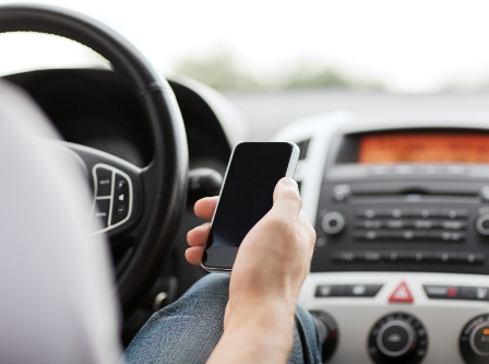 Image of a driver texting while behind the wheel