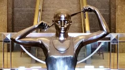 Sculpture of woman blindfolding herself as a symbol of justice at the Warren B. Rudman Courthouse in Concord, NH