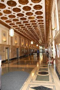 Medium shot of renovated interior hallway with ornamental ceiling and period lighting fixtures