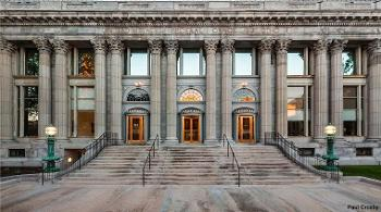 Medium street-level shot of the Minneapolis Federal Building front entrance with restored bronze doors