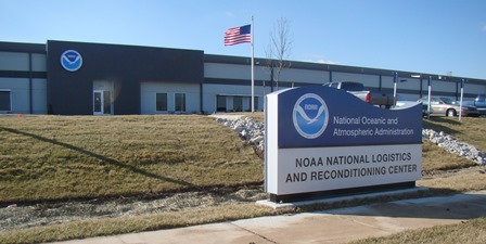 Front of new NOAA location with NOAA Seal on the building behind a sign saying National Oceanic and Atmospheric Administration NOAA National Logistics and Reconditioning Center