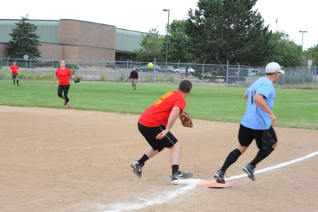 Image of people playing outfield in a softball game