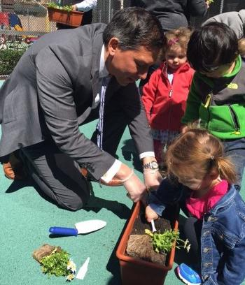 Public Buildings Service Commissioner Norm Dong plants flowers with the Fedkids in New York City