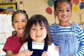 Head and shoulders stock photo shot of three children in a child care center