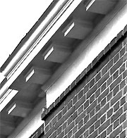 close up, exterior of building showing square blocks extending from the bottom of the roof eaves