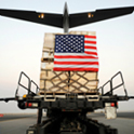 flag-draped cargo being loaded onto airplane