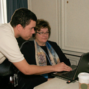 Man helping a woman with a computer application