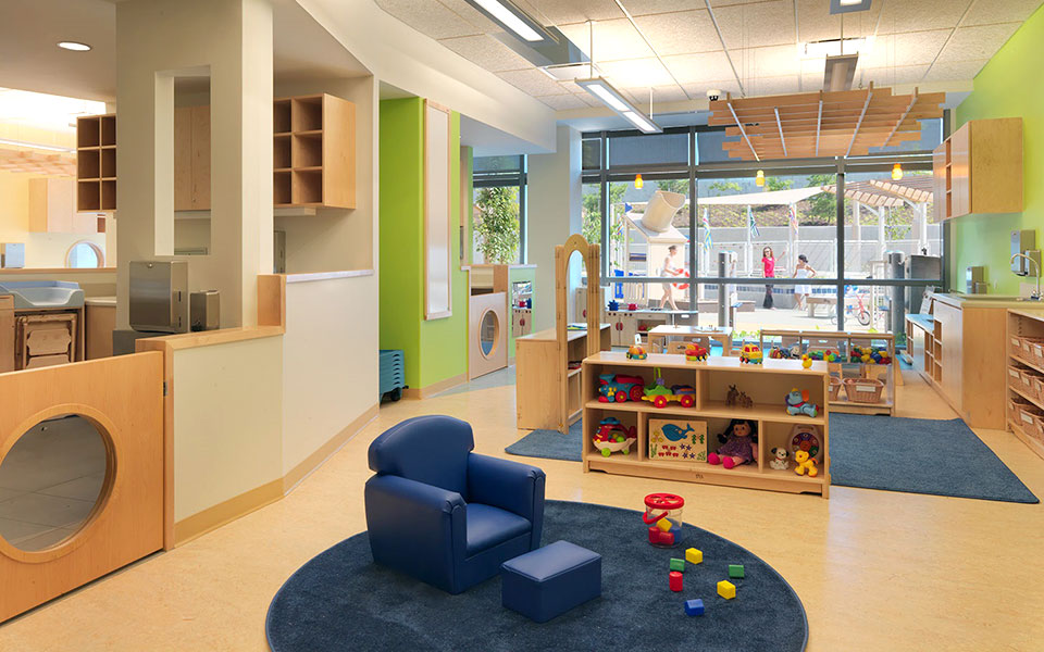 Interior of a GSA childcare center with tables, play areas, shelves, toys