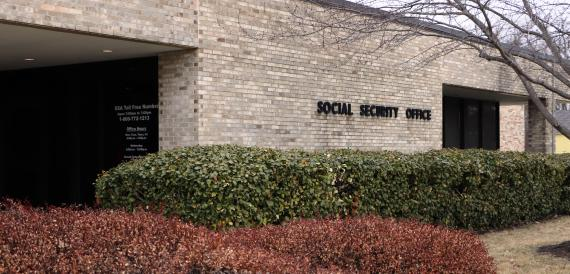 A brick building with the words Social Security Office on it; the SSA Toll Free Number Open 7 a.m. to 7 p.m. 1-800-772-1213 and office hours Monday, Tuesday, Thursday and Friday 9 a.m. to 4 p.m., Wednesday 9 a.m. to noon, closed federal holidays are printed on a glass wall.