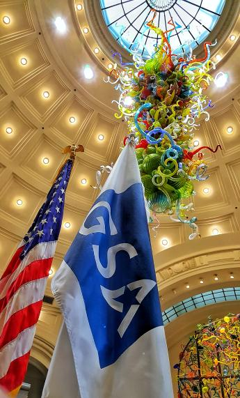 Picture of American Flag and GSA Star Mark Flag inside the Tacoma Union Station, backdrop is the Chihuly glass and Tacoma Union Station Dome
