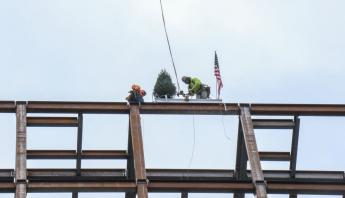Photo courtesy of Hill International: The last steel beam is hoisted and set into place for the new U.S. Courthouse in Harrisbur