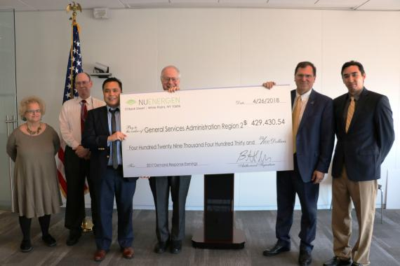 Employees pose for photo with ceremonial check