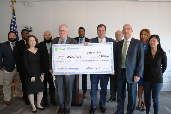 Employees from GSA, ConEdison and Trane pose for a photo with a ceremonial check