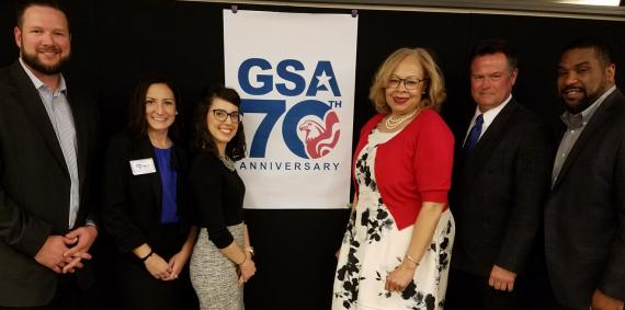 Medium shot of the organizers of the R5 PBS Reverse Industry Day with GSA 70th Anniversary logo behind