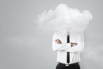 Person in a tie standing with head obscured by cloud