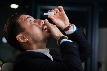Man putting in eyedrops