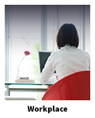 Woman at a laptop looking out a large window with text Workplace
