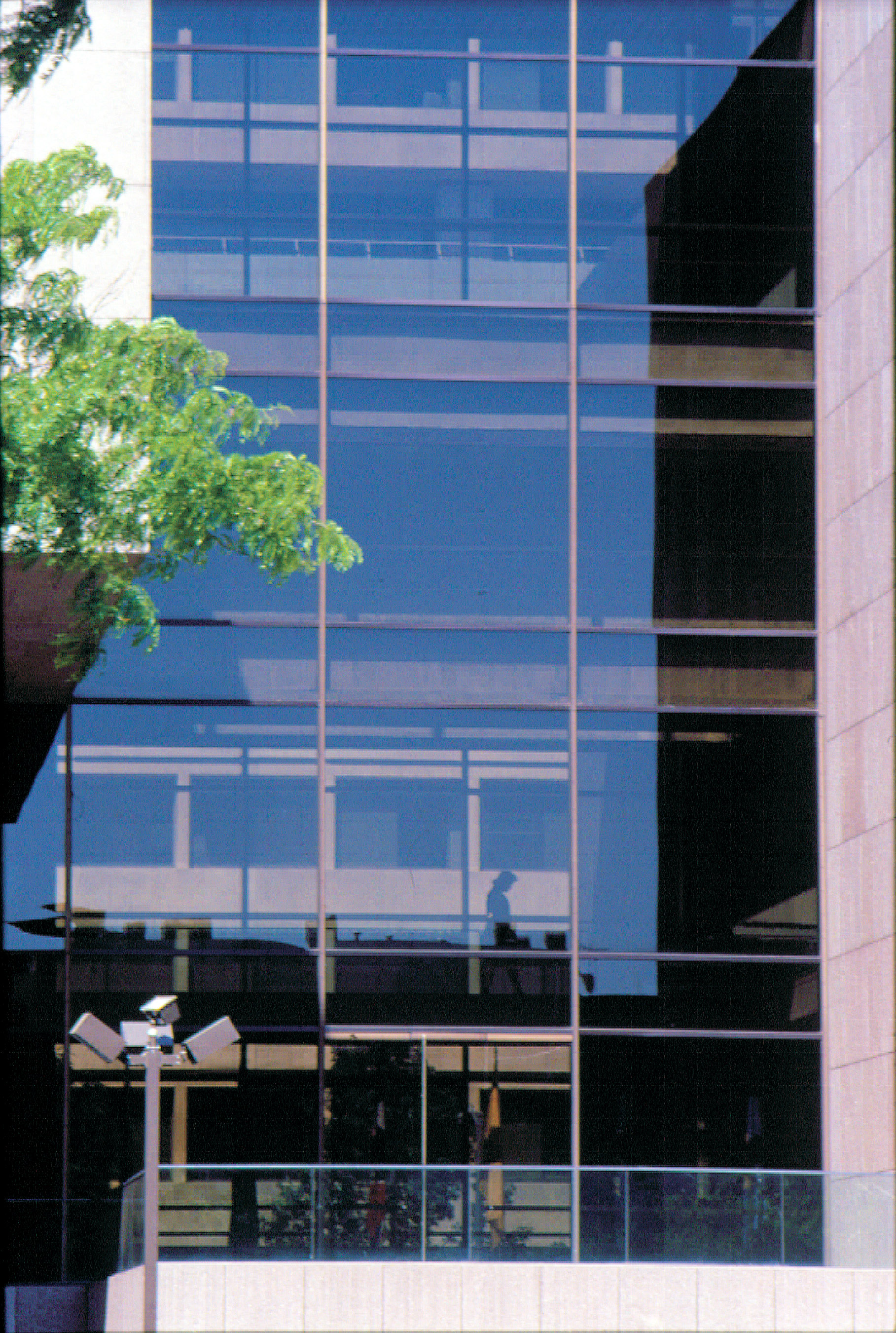 Detail of the central cantilevered glass block fronting the landscaped plaza on 2nd Street, NW. The glass is bronze-tinted with slim bronze-anodized aluminum mullions.